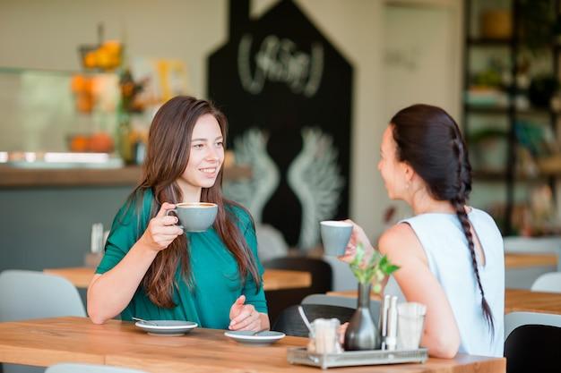 Gelukkige glimlachende jonge vrouwen met koffiekoppen bij koffie. communicatie en vriendschapsconcept Premium Foto