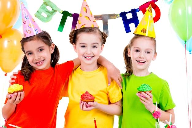 Gelukkige glimlachende meisjes die kleurrijke cakes houden - die op een witte achtergrond worden geïsoleerd. Gratis Foto