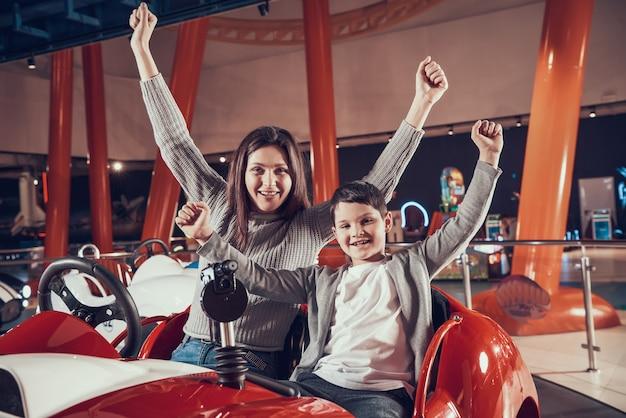 Gelukkige glimlachende moeder en zoonszitting op stuk speelgoed auto. Premium Foto