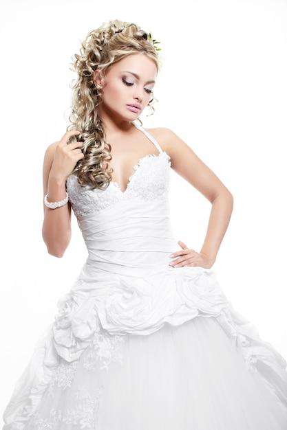 Gelukkige glimlachende mooie bruid in witte huwelijkskleding met kapsel en heldere make-up Gratis Foto