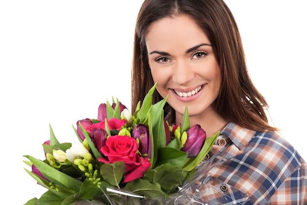 Gelukkige glimlachende mooie jonge vrouw met boeket Gratis Foto
