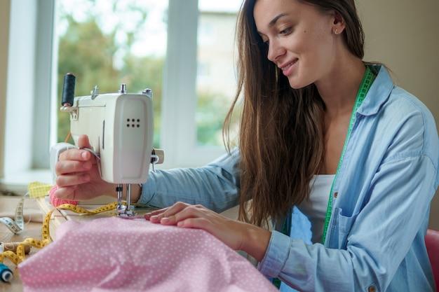Gelukkige glimlachende naaister met elektrische naaimachine en verschillende naaiende toebehoren voor het naaien van kleren op het werk Premium Foto