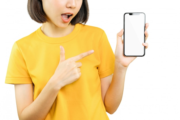 Gelukkige glimlachende vrouw die met hand en vinger aan slimme telefoon met verbaasd voor succes richten. Premium Foto
