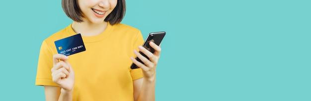 Gelukkige glimlachende vrouw die slimme telefoon en creditcard houden met online het winkelen. Premium Foto