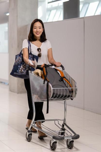Gelukkige glimlachende vrouw met bagage in kar op de luchthaven. Premium Foto