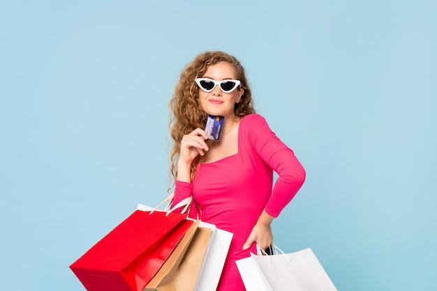 Gelukkige glimlachende vrouw met het winkelen zakken die creditcard tonen Premium Foto