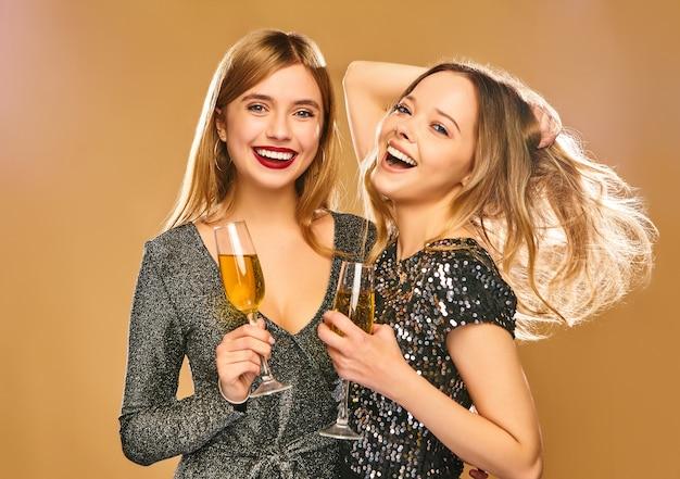 Gelukkige glimlachende vrouwen in modieuze betoverende kleding met champagneglazen op gouden muur Gratis Foto