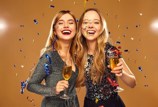 Gelukkige glimlachende vrouwen in stijlvolle glamoureuze jurken met champagneglazen onder confetti Gratis Foto