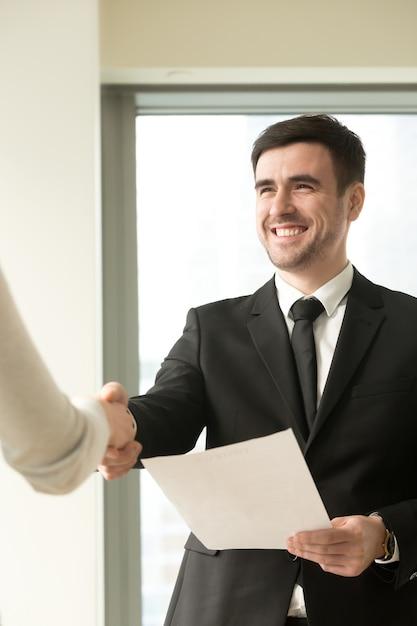 Gelukkige glimlachende zakenman die kostuum draagt die vrouwelijke hand schudt Gratis Foto
