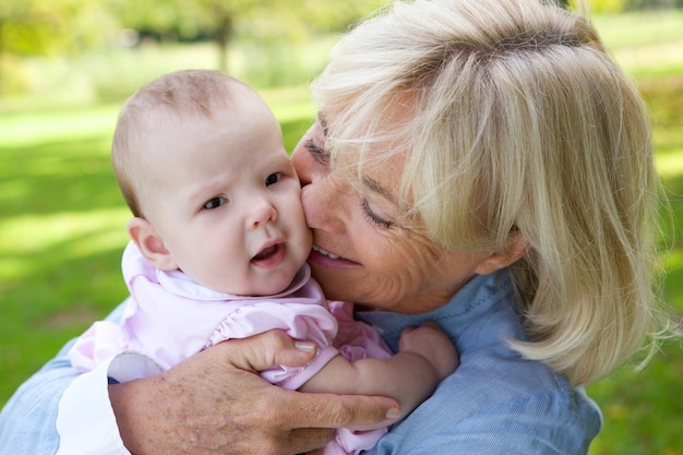 Gelukkige grootmoeder die leuke baby houdt Premium Foto