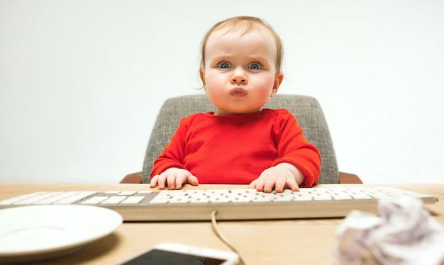 Gelukkige het meisjeszitting van de kindbaby met toetsenbord van moderne computer of laptop die op een witte studio wordt geïsoleerd Gratis Foto
