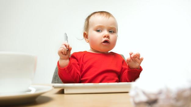 Gelukkige het meisjeszitting van de kindbaby met toetsenbord van moderne computer of laptop in witte studio Gratis Foto