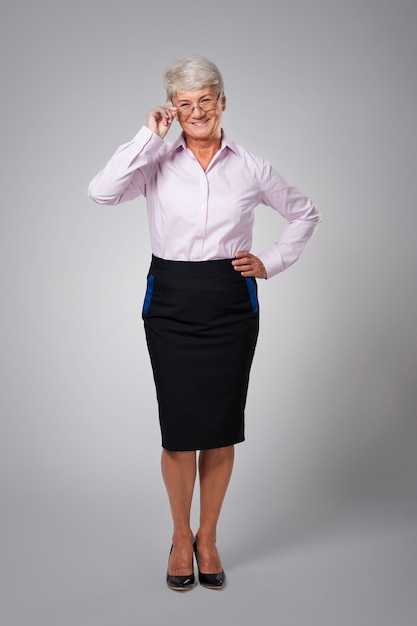 Gelukkige hogere bedrijfsvrouw die glazen draagt Gratis Foto