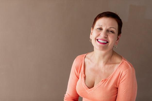 Gelukkige hogere vrouw die camera bekijkt Gratis Foto