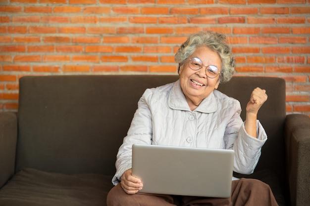Gelukkige hogere vrouw gezet op bank in laptop van het woonkamergebruik, oudere generatie die modern technologieconcept gebruiken. Premium Foto