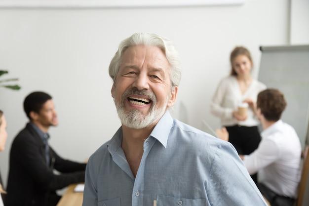 Gelukkige hogere zakenman lachen die camera in bureau, portret bekijkt Gratis Foto