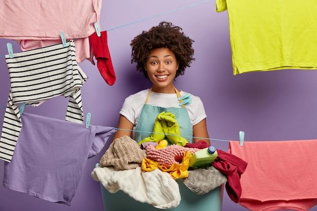 Gelukkige huisvrouw tevreden om huishoudelijk werk op tijd af te maken, druk bezig met de was, staat naast een hoop ongevouwen vuil linnen in een mand, gekleed in een casual blauw schort. schoonmaakdag en dagelijkse routine concept Gratis Foto