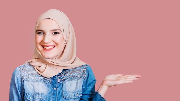 Gelukkige islamitische vrouw die iets op achtergrond voorstelt Gratis Foto