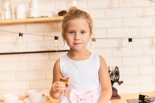 Gelukkige jeugd, plezier en vreugde concept. binnen schot van lief schattig babymeisje mooie jurk dragen aan eettafel in stijlvolle keuken interieur, lachen, kauwen heerlijk koekje of taart Gratis Foto