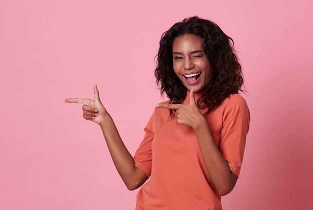 Gelukkige jonge afrikaanse vrouw die zich met haar vinger bevindt die op roze achtergrond richt Premium Foto