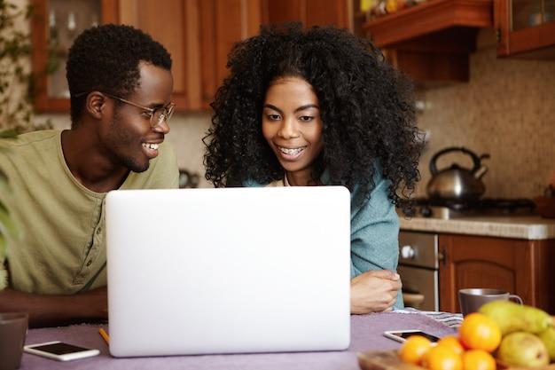 Gelukkige jonge afro-amerikaanse familie zittend aan de keukentafel, surfen op internet op generieke laptop pc, online winkelen, op zoek naar huishoudelijke apparaten. mensen, moderne levensstijl en technologie concept Gratis Foto