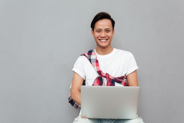 Gelukkige jonge aziatische mens die laptop met behulp van Gratis Foto