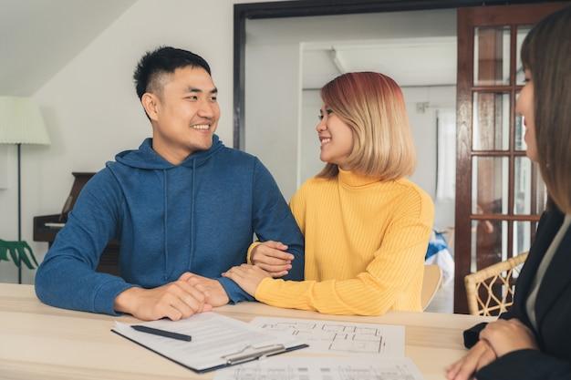Gelukkige jonge aziatische paar en makelaar in onroerend goed Gratis Foto