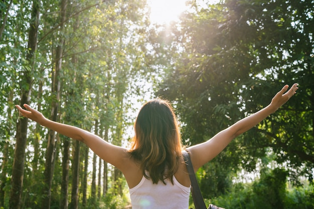 Gelukkige jonge aziatische vrouwenreiziger die met rugzak in bos lopen. Gratis Foto