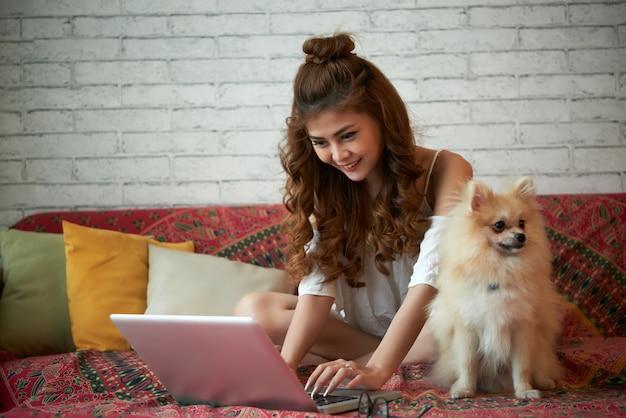 Gelukkige jonge aziatische vrouwenzitting op laag thuis met kleine huisdierenhond en het gebruiken van laptop Gratis Foto