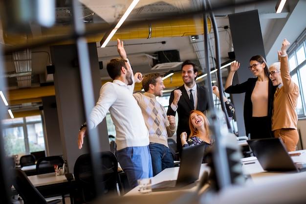 Gelukkige jonge bedrijfsmensen die zich in het bureau bevinden en op succes in het bureau verheugen Premium Foto
