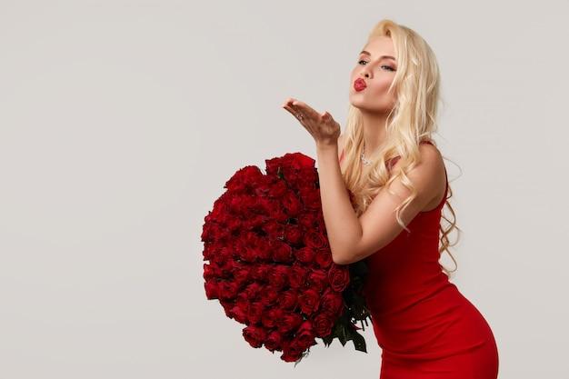Gelukkige jonge blonde vrouw die een groot boeket van rode rozen als een geschenk voor 8 maart of valentijn. ze blaast een kus. neutrale grijze achtergrond Premium Foto