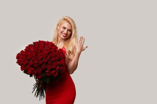 Gelukkige jonge blonde vrouw die een groot boeket van rode rozen als een geschenk voor 8 maart of valentijn. ze wijst naar de verlovingsring om haar vinger. Premium Foto