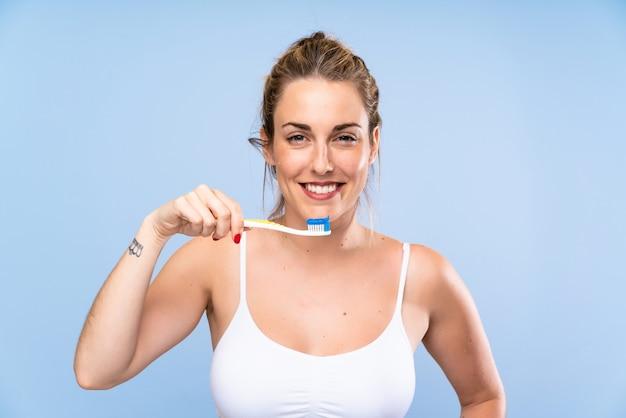 Gelukkige jonge blondevrouw die haar tanden poetsen Premium Foto