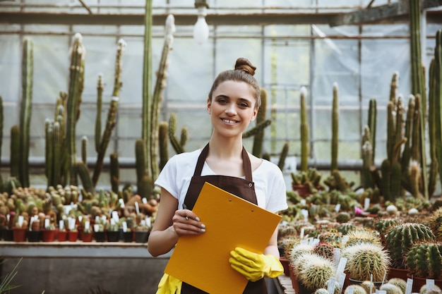 Gelukkige jonge dame die zich in het klembord van de serreholding bevinden Gratis Foto