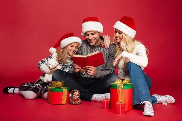 Gelukkige jonge familie die kerstmishoeden geïsoleerd zitten dragen Gratis Foto