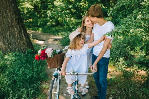 Gelukkige jonge familie het besteden tijd samen buiten. vadermoeder en hun kind in het groene park Premium Foto