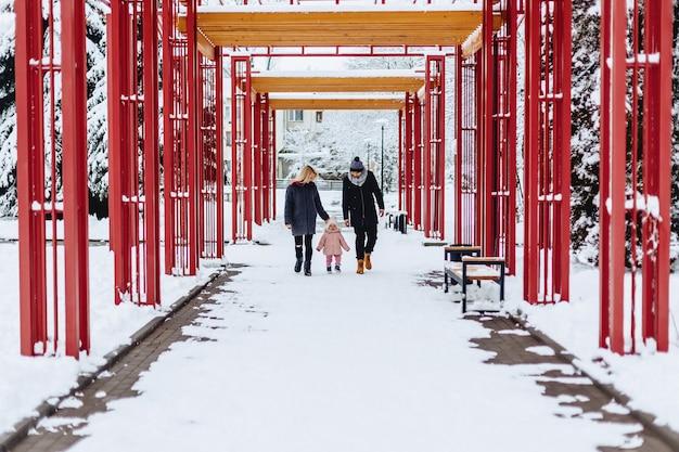 Gelukkige jonge familie loopt met baby op winter straat, moeder, vader, kind Premium Foto