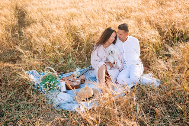 Gelukkige jonge familie op picknick in geel tarweveld Premium Foto
