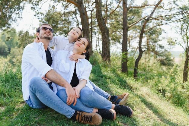 Gelukkige jonge familie tijd buiten doorbrengen op een zomerdag, veel plezier in het prachtige park Premium Foto