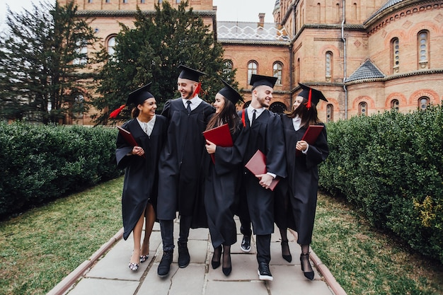 Gelukkige jonge gediplomeerde studenten in capes met diploma's die op tuinuniversiteit lopen. Premium Foto