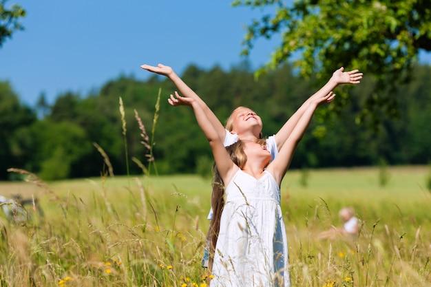 Gelukkige jonge geitjes in een weide die hun handen omhoog in de hemel opheft Premium Foto