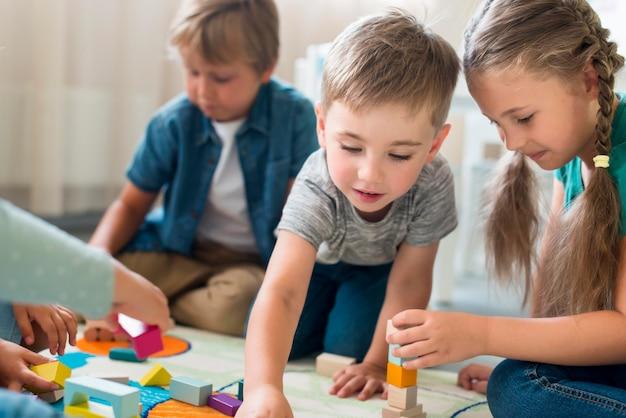 Gelukkige jonge geitjes samenspelen in de kleuterschool Premium Foto