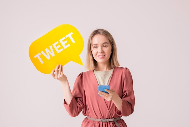 Gelukkige jonge glimlachende vrouwelijke duizendjarige met geel papier tekstballon posten in haar profiel terwijl ze online communiceert Premium Foto