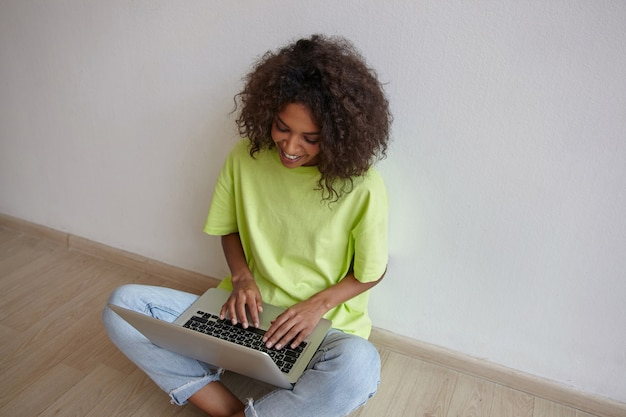 Gelukkige jonge krullende vrouw met donkere huid chatten met vrienden op laptop, zittend met gekruiste benen, spijkerbroek en geel t-shirt dragen Gratis Foto