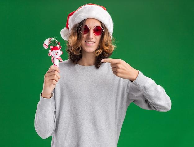 Gelukkige jonge man met kerst kerstmuts en rode bril met kerst candy cane kijken naar camera glimlachend wijzend met wijsvinger naar het staande op groene achtergrond Gratis Foto