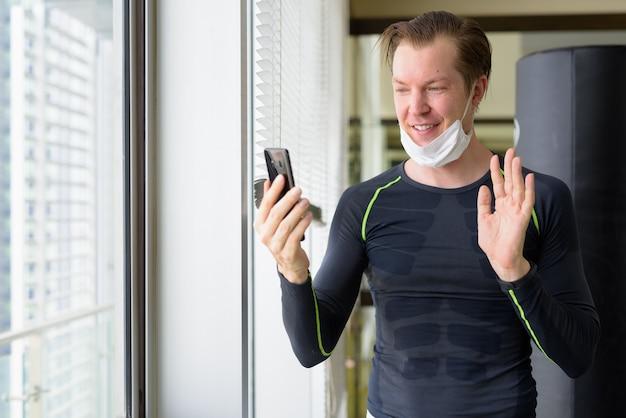 Gelukkige jonge man met masker videogesprek en klaar om te trainen tijdens covid-19 Premium Foto