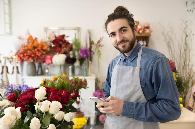 Gelukkige jonge mannelijke bloemist die het mobiele telefoon in hand kijken aan camera houden Gratis Foto