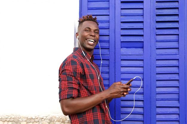 Gelukkige jonge mens die in openlucht het luisteren muziek met mobiele telefoon bevindt zich Premium Foto