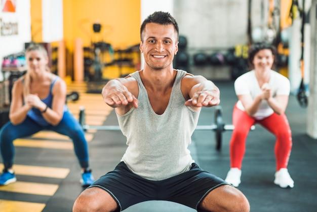 Gelukkige jonge mens die opwarmingsoefening in gymnastiek doet Gratis Foto
