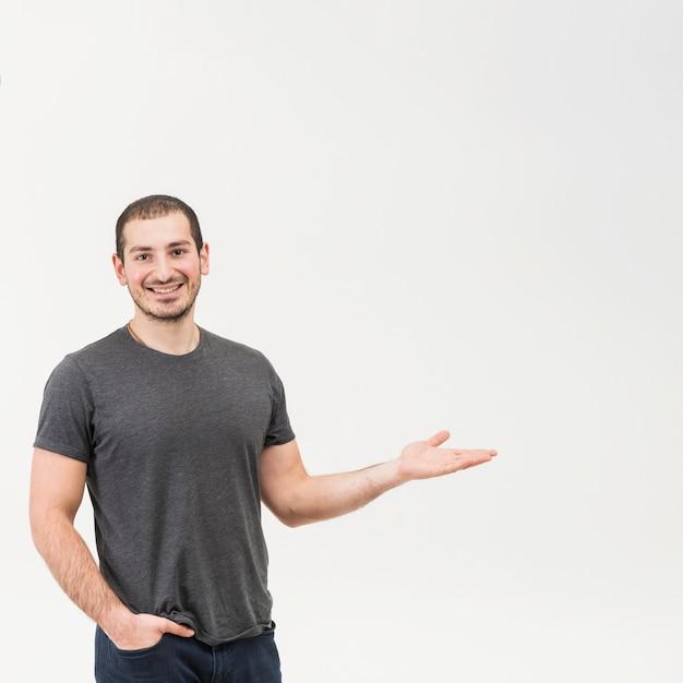 Gelukkige jonge mens die over witte achtergrond voorstellen Gratis Foto